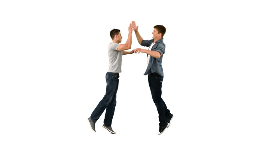 Two guys high-fiving one another in slow motion against a white background
