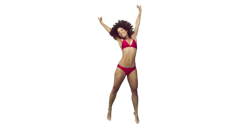 Woman in a red bikini jumping in slow motion against a white background