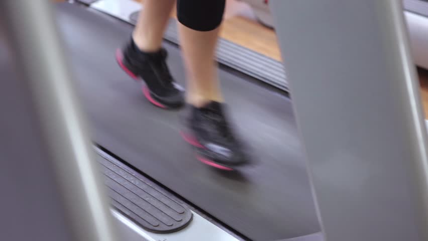 Sport, fitness, lifestyle, technology and people concept - close up of woman legs walking on treadmills in the gym. | Shutterstock HD Video #22144960