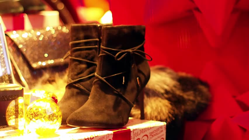 Elegant women's winter black boots with high heels placed in a showcase shop-window of a glamour boutique at Christmas sale time on a busy street. Grafton street, Dublin, Ireland.   Shutterstock HD Video #22151467