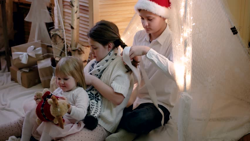 Brother Braided Pigtails to to His Little Sister in New Year and Christmas Decorations | Shutterstock HD Video #22187962