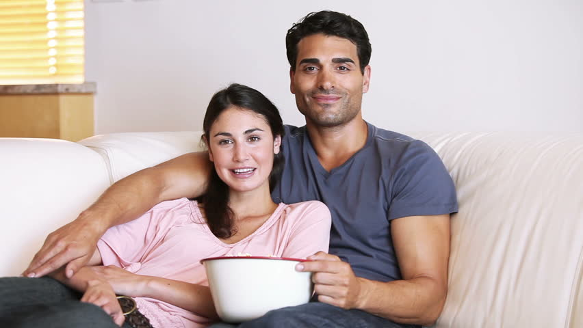 Laughing couple watching the television in the living room for Living room ideas young couples