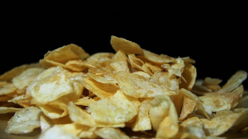 Potato Chips Rotating On Black Background. Slow Motion in 96 fps. Potato chips are rotated on a black background. Close-up of yellow delicious chips randomly lying on a table.  | Shutterstock HD Video #22231315