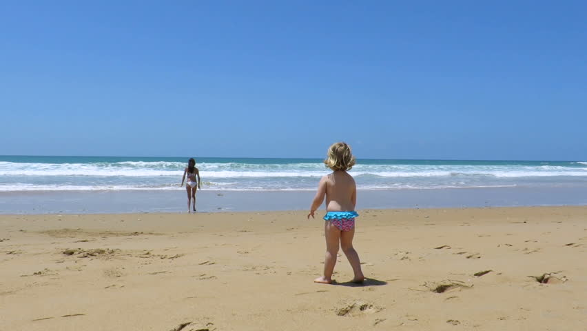 Woman in the distance at seashore calling and asking with hand to two years old blonde baby back with blue and red swimsuit at sand beach     Shutterstock HD Video #22254220