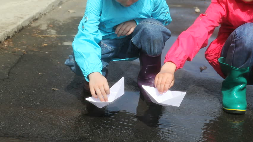 Children Playing With Paper Boats After The Rain Stock