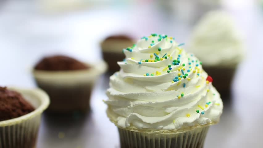 Process of making delicious cupcakes in a bakery shop, Close up of hand sprinkling topping onto fresh cupcakes #22393891