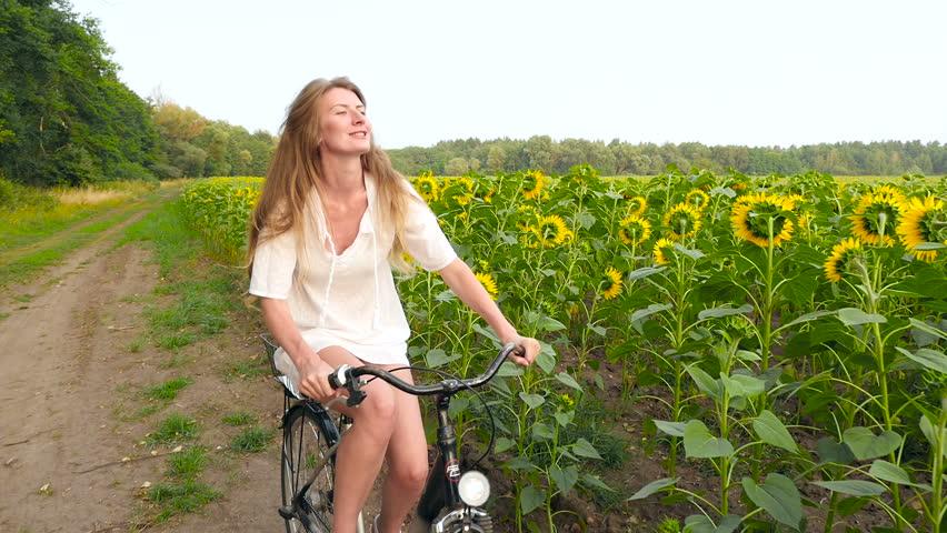 Girl rides a bike at sunflower field | Shutterstock HD Video #22443976
