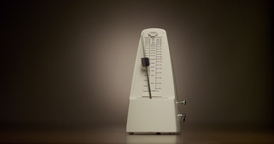 Mechanical metronome produces an audible beat at regular intervals that the user can set in beats per minute. White metronome on dark background using vignetting. | Shutterstock HD Video #22460338