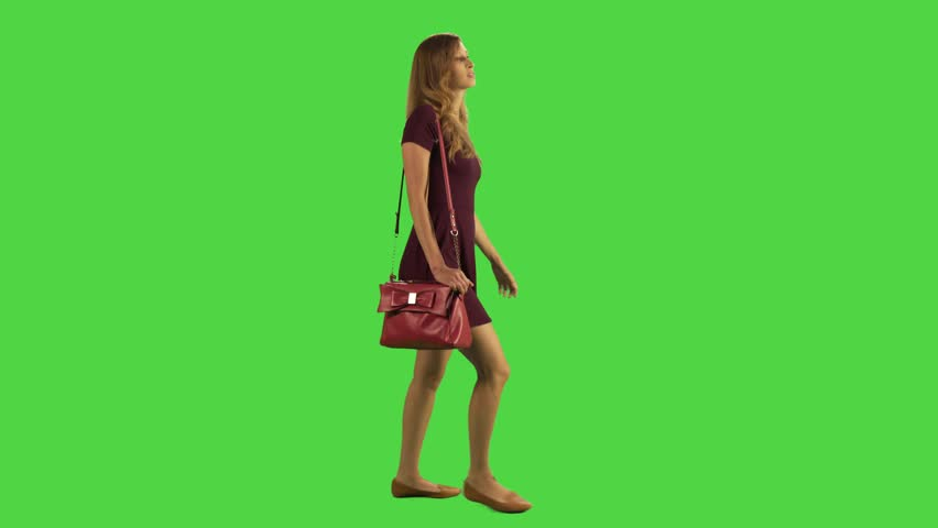 Young woman walking sideways feeling ill and upset in a full body shot over a green screen. | Shutterstock HD Video #22489957