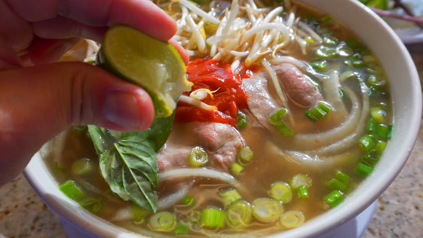 Squeezing slice of lime into Pho soup bowl #22510252