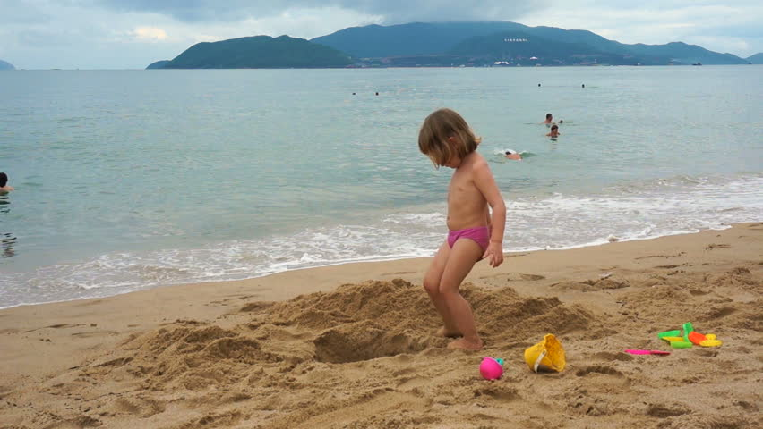 A child plays in the sand at the sea. In the background, unrecognizable people bathe in the sea. | Shutterstock HD Video #22559491