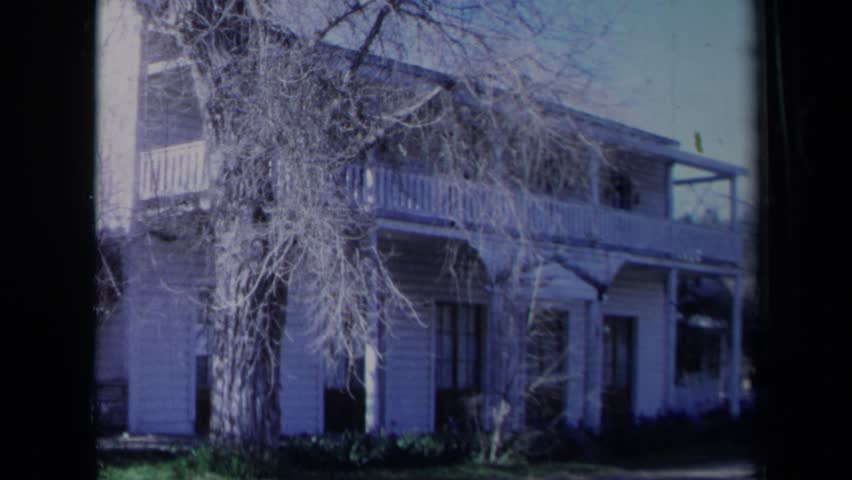 CALIFORNIA 1969: leafless trees stand outside of white clapboard house with second floor terrace