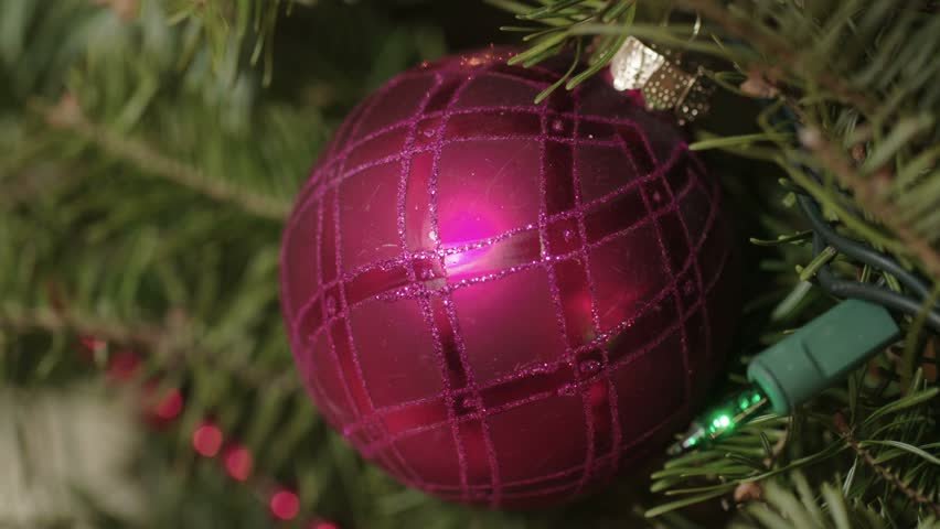 Dolly slider movement past a red ornament decorating a Christmas tree. Shot in 4K UHD.   Shutterstock HD Video #22769623