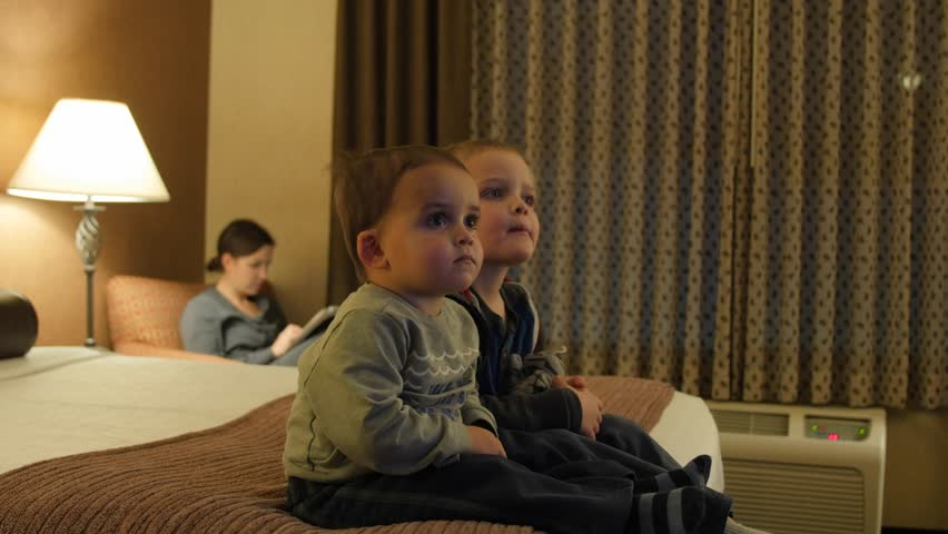 Adorable little boys watching the Television in their hotel room at night with their family #22935790