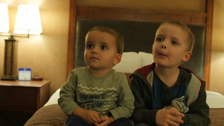 Adorable little boys watching the Television in their hotel room at night with their family #22935799