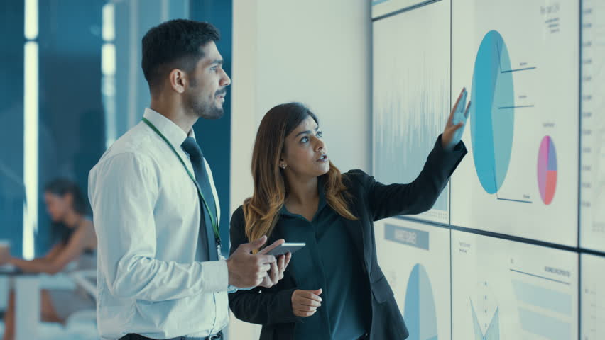 4KBusinessman & woman in discussion looking at video screen with charts & graphs Dec 2016-UK | Shutterstock HD Video #22985875