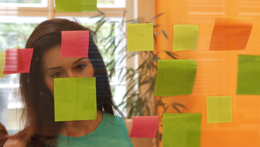 Beautiful female executive reading sticky notes in office 4k | Shutterstock HD Video #23008996