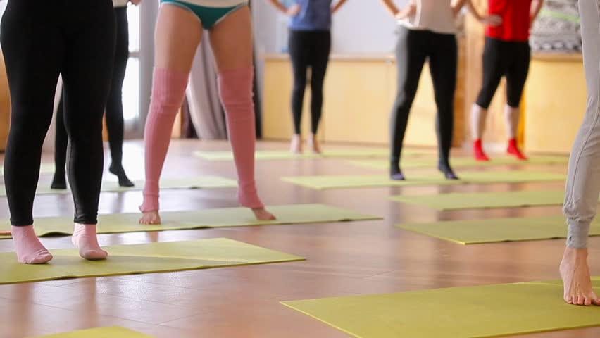 Young women swing legs. Women train muscles of legs. In the special hall. Women train legs on special rugs. Group of young women in fitness | Shutterstock HD Video #23053321