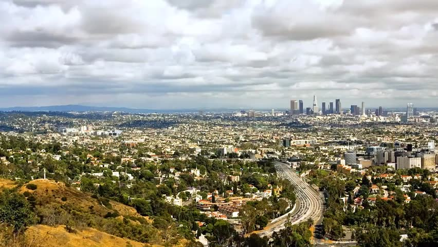 Los Angeles in Cloudy Weather. the Clouds Float Across the Sky and Cast Its Shadow Over the City. a View of the Wide Road, the Road Goes a Lot of Cars. on the Side of the Road Grow Green Trees. Far | Shutterstock HD Video #23112343