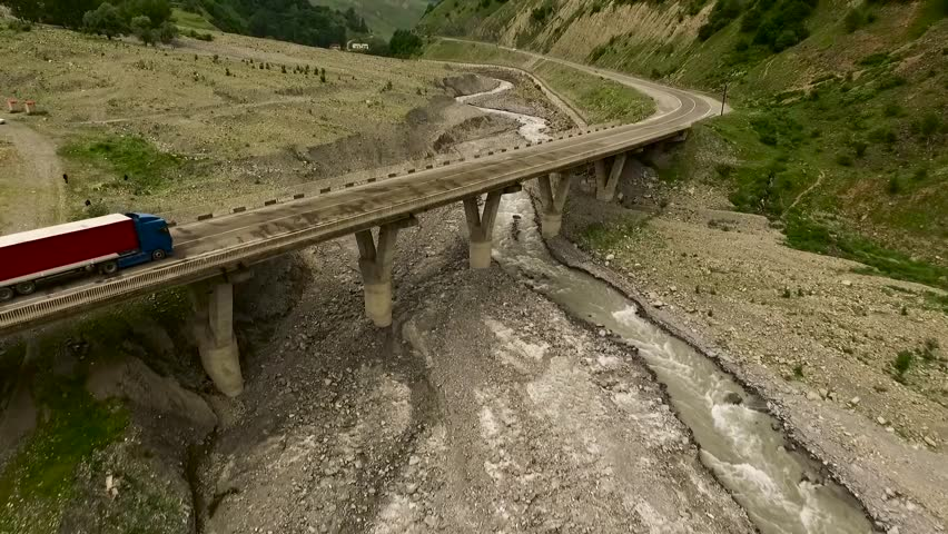 AERIAL: mountain river with a bridge on which the truck travels | Shutterstock HD Video #23158198