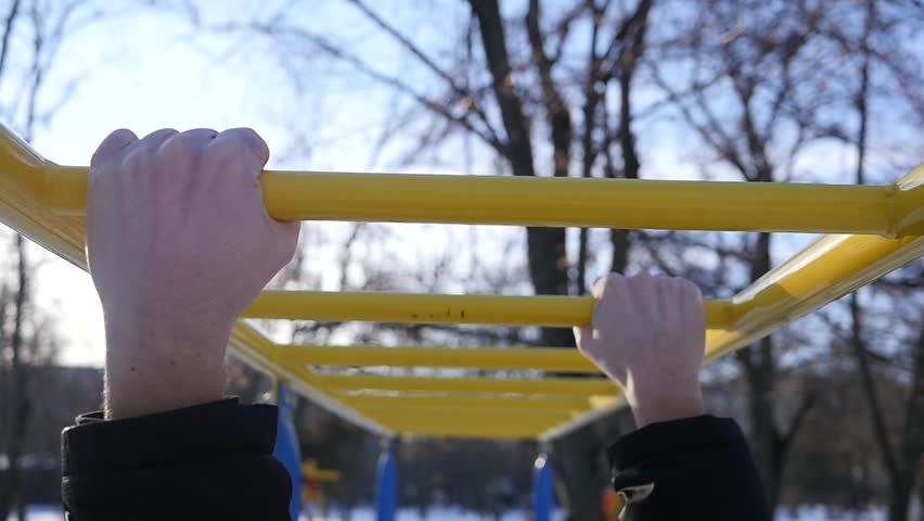 Body care man hands on horizontal bar on outdoors park sports ground athletic field | Shutterstock HD Video #23159953