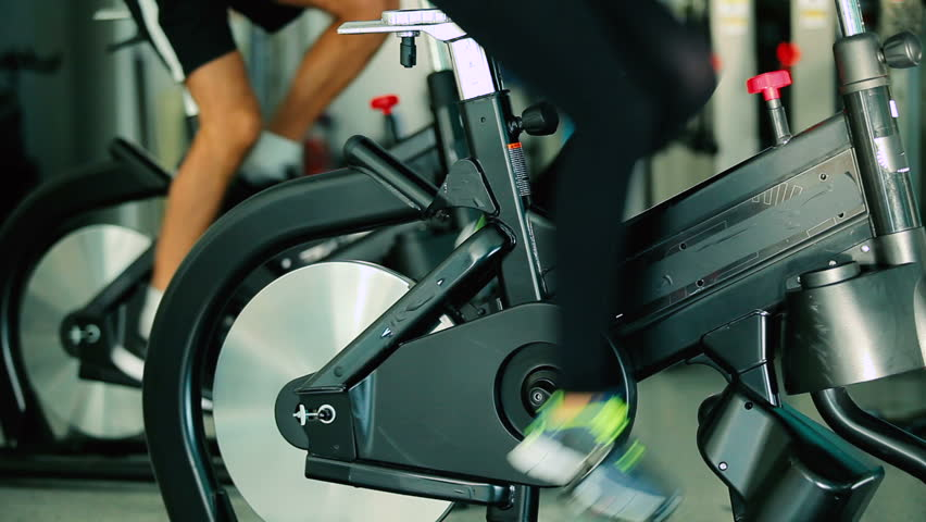 Close-up - sports people pedaling on the exercise bicycle in the gym | Shutterstock HD Video #23162068