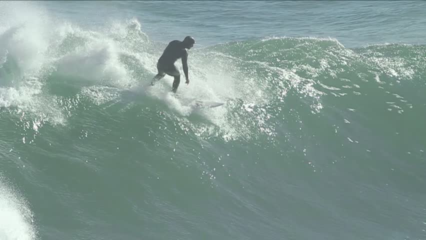 Man surfing as waves crash behind him (slow-motion). Pichilemu, Chile - Feb 2016) | Shutterstock HD Video #23165857