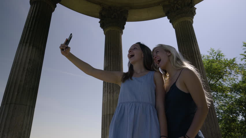 Young Women Take Funny Selfies In The The Temple De La Sibylle In The Parc Des Butte Chaumont In Paris, France | Shutterstock HD Video #23180878