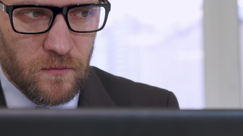 Middle aged businessman working on laptop at the office. Close up of caucasian bearded man in glasses looking at the screen. Attractive serious male manager in suite and tie doing his job | Shutterstock HD Video #23187070