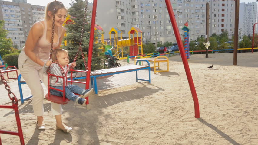 Happy young mother swinging her baby son on swings at playground | Shutterstock HD Video #23193640