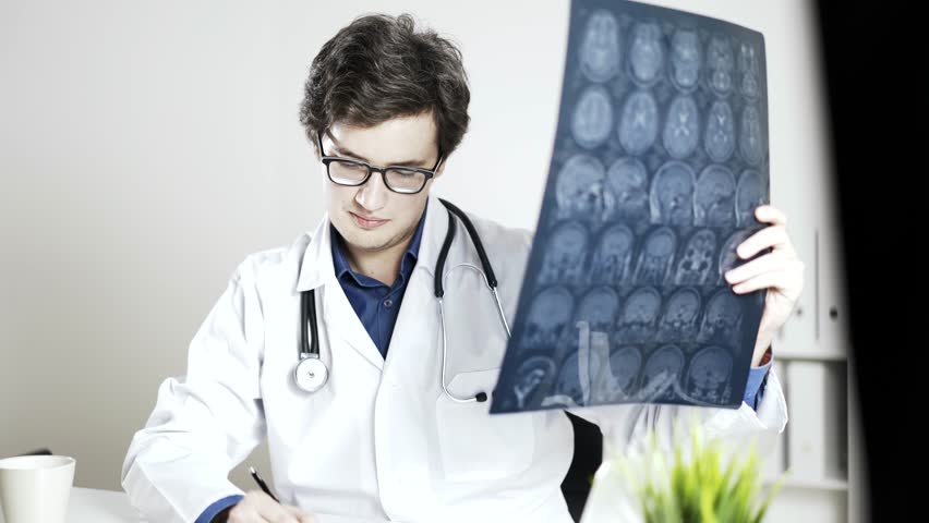 A neurologist is examining brain x-ray and making some notes. A concept of successful medical practice. Locked down real time medium shot. | Shutterstock HD Video #23211937