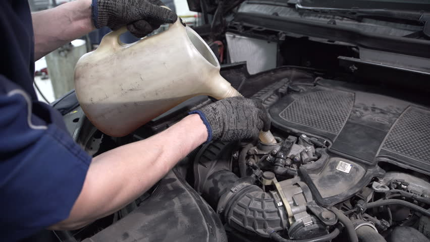 Specialist the service station to fill in oil using a watering can. | Shutterstock HD Video #23212261