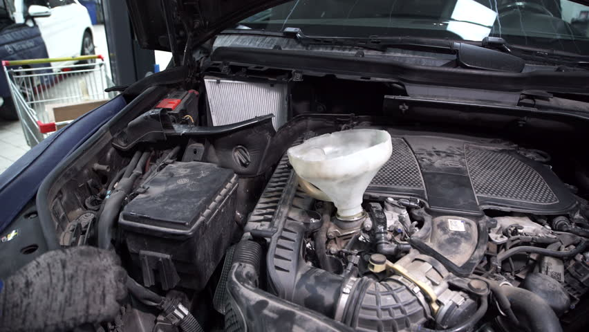 In service station mechanic through a funnel pour oil in a car engine. | Shutterstock HD Video #23212270