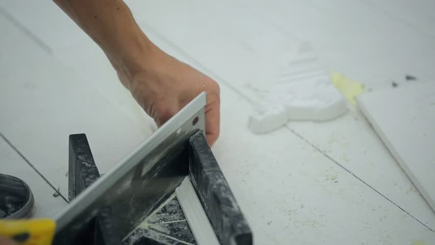 Man cuts plinth with special equipment, saw to decorate room. Close up hands of male doing repairs, cutting plinths with tools. Holding device helps to hold white blanch, clips unnecessary parts with | Shutterstock HD Video #23213161