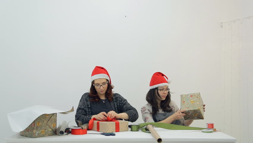 Two women decorate gifts with ribbons for Christmas, New Year. In front of us Asian with black flowing hair, in sweater with flower pattern, gray apron, with silver ring on right hand, Female with red | Shutterstock HD Video #23213170