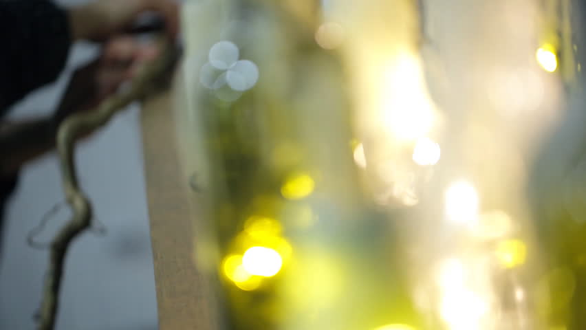 Woman decorates room for the New Year. In the foreground you can see white candles inserted in a green glass bottle close up. Near lie large thick white candles of various sizes and pine cones on | Shutterstock HD Video #23213179