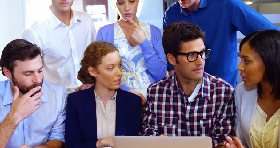 Group of business executives discussing over laptop | Shutterstock HD Video #23226535