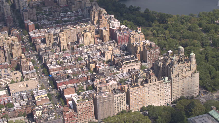 AERIAL: Flying above Upper West side overlooking lush green Central Park in sunny New York City. Luxury condominium apartment buildings with Central Park view along the busy avenue full of yellow cabs | Shutterstock HD Video #23257810