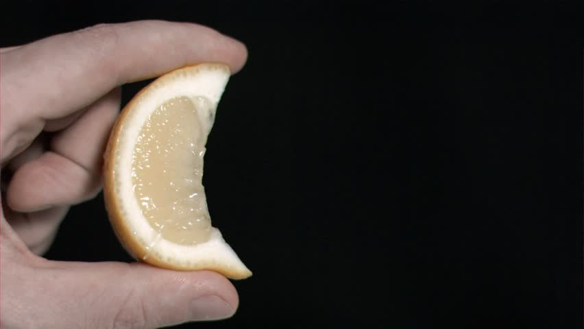 Lemon in super slow motion being squeezed against a black background