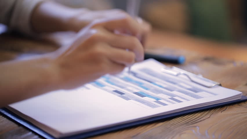 Close up woman hands writing filling in table in folder inside office. Woman holds blue pen, writes, fills documents indoors. Businesswoman hand over application form in business plan, meeting | Shutterstock HD Video #23503627