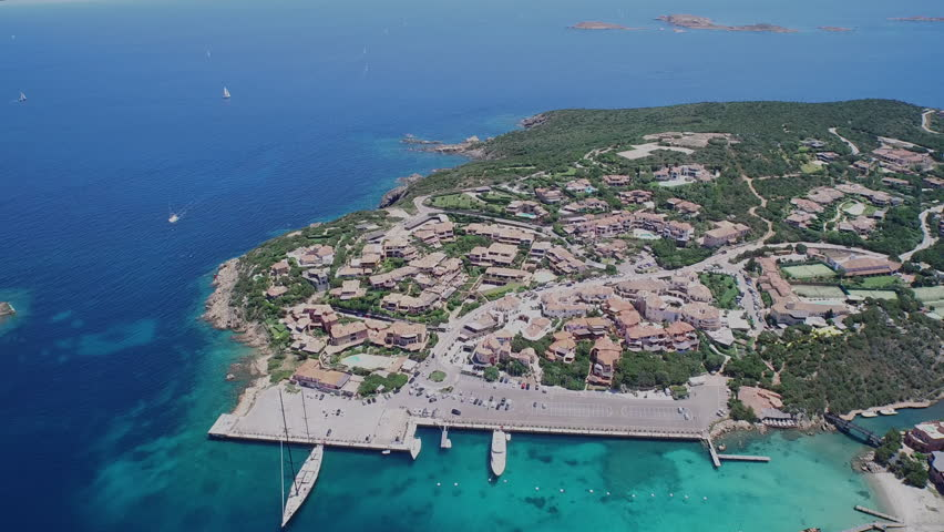 Small sailboat harbor in Sardinia from drone Drone camera descends above a small port with shallow water and sailboats in Sardinia. | Shutterstock HD Video #23535487
