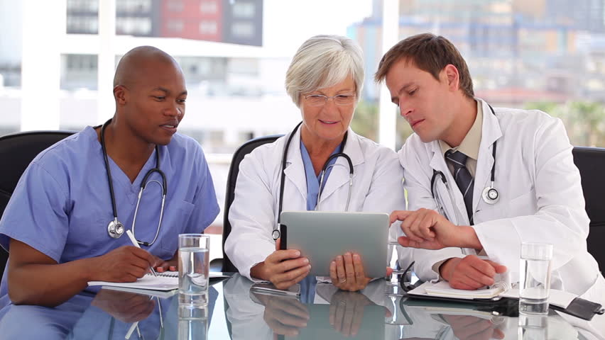 Serious medical team looking at a tablet computer in a bright office - HD stock footage clip