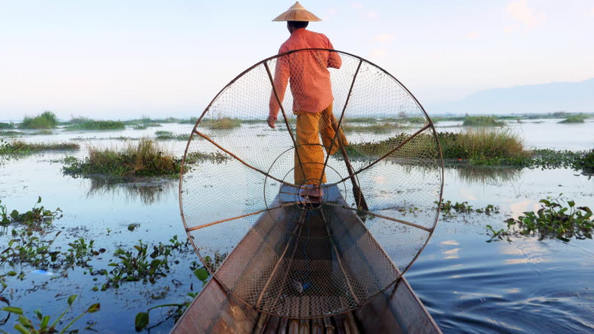 Inle Lake fisherman rowing boat in traditional style at sunrise, Shan State, Myanmar (Burma).