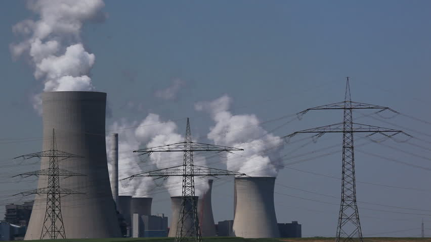 Brown coal power plant with huge cooling towers and steam