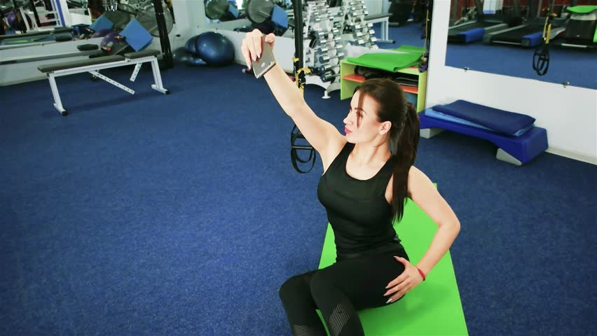 Young sports woman using phone, girl athlete selfie in the gym, Communication in Internet, fitness, lifestyle, technology and people, Sporty girl smiling at camera making selfie picture at gym, | Shutterstock HD Video #24027148