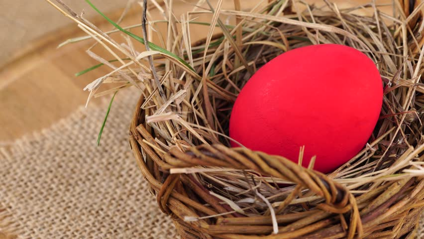 Close up shot of a red Easter egg in woven basket with dry grass rotating against beige background. Egg in a nest concept. | Shutterstock HD Video #24027778