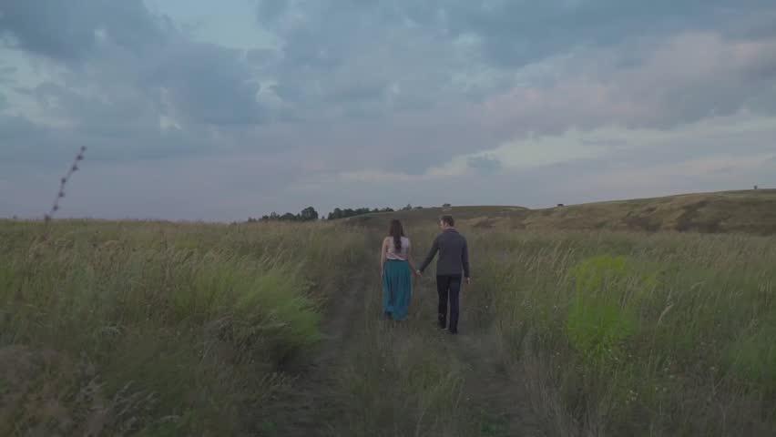 Couple walking in a field. | Shutterstock HD Video #24102676