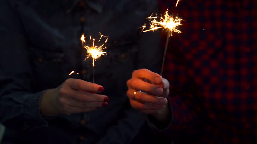 Happy couple holding sparklers, hugging and smiling while celebrating Christmas | Shutterstock HD Video #24107212