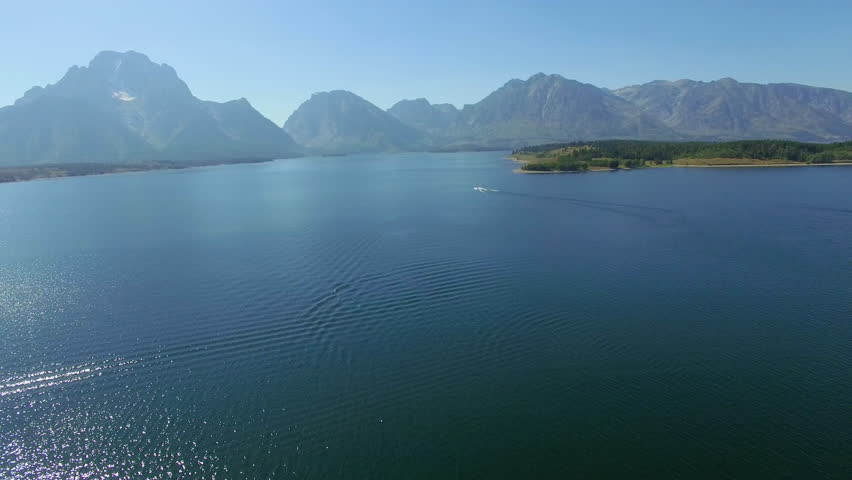 A boat speeds across Jackson Lake as the camera pans right to reveal a shoreline | Shutterstock HD Video #24108193