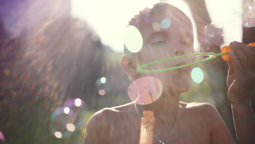 Young handsome boy blowing bubbles outdoors on sunny day in summer on sunshine background with blurred beautiful bokeh. 1920x1080. hd | Shutterstock HD Video #24109948
